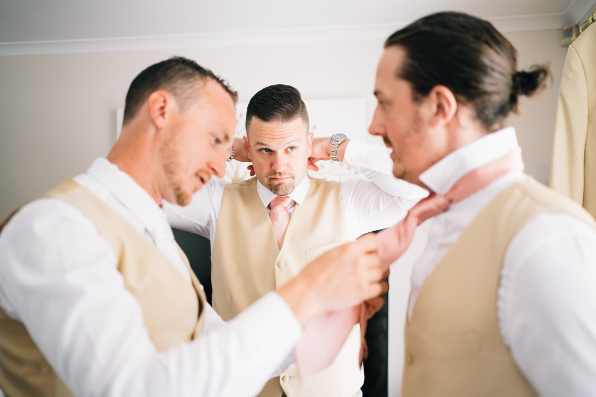 Groom helping groomsman with tie at home