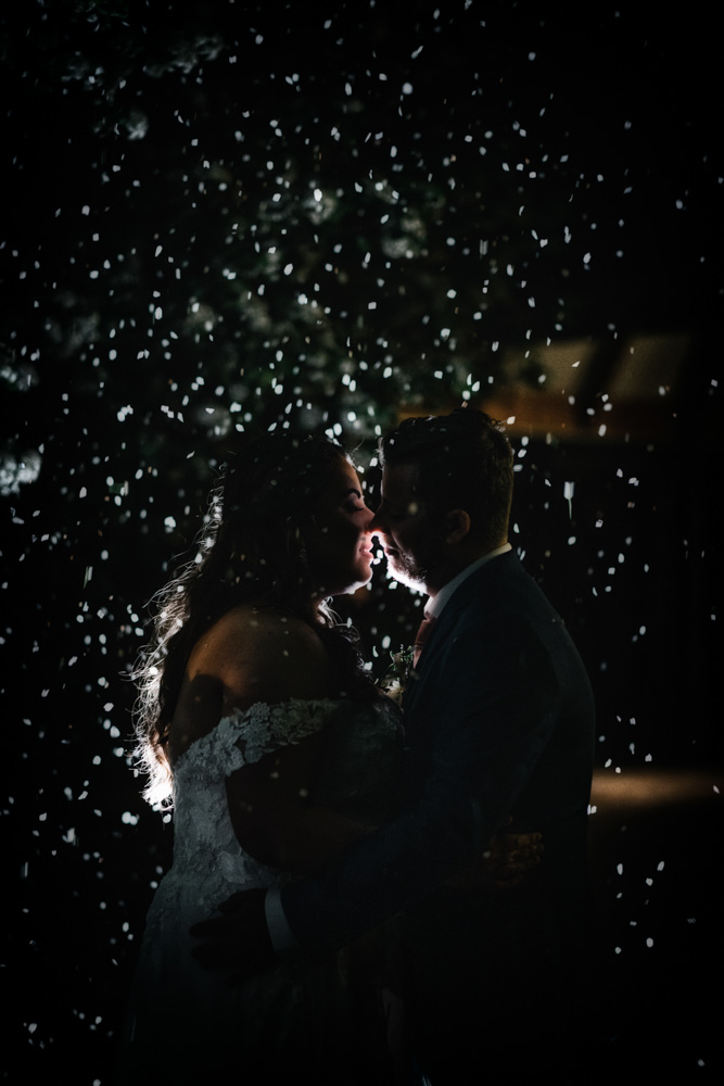 bride and groom kissing in snowfall