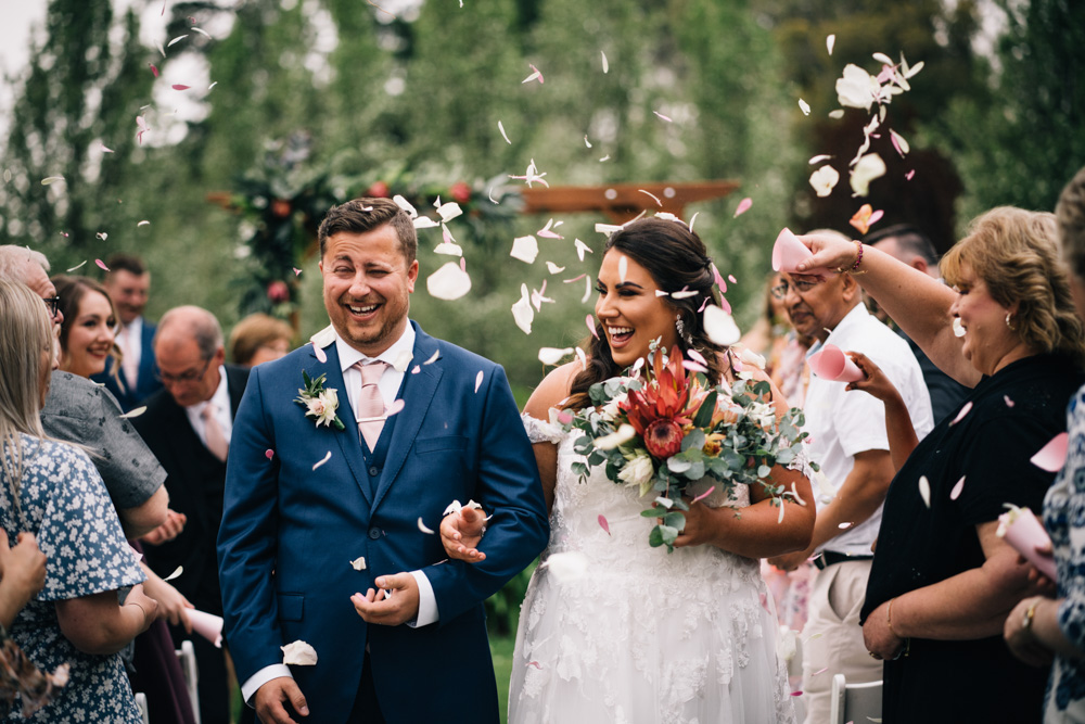 bride and groom being showered with flower petals