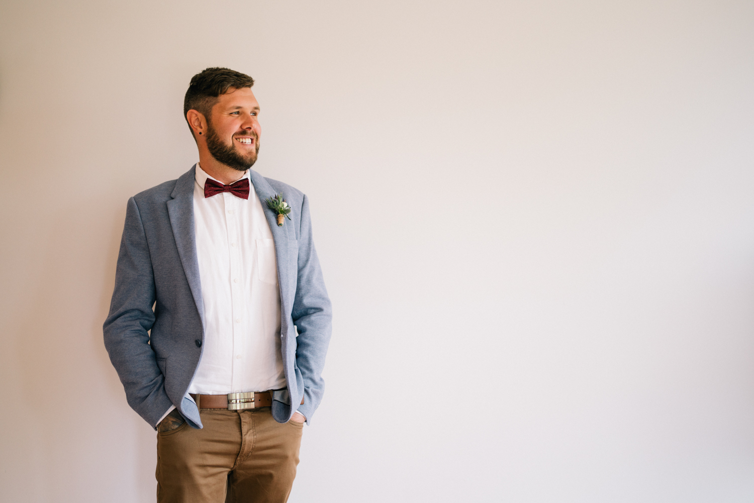 Groom standing by wall
