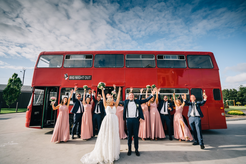 bridal party in front of big red bus