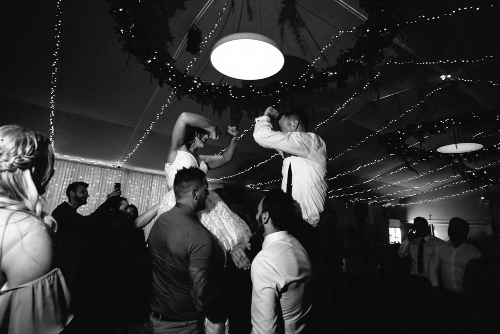 Bride & Groom Dancing on Shoulders of wedding guests