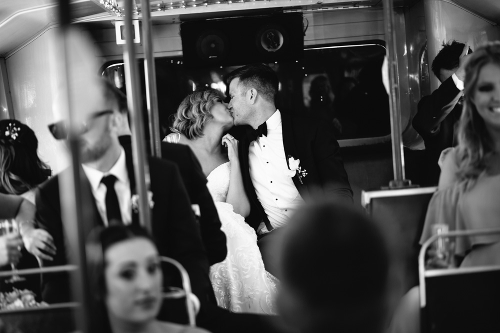 bride and groom kissing on bus