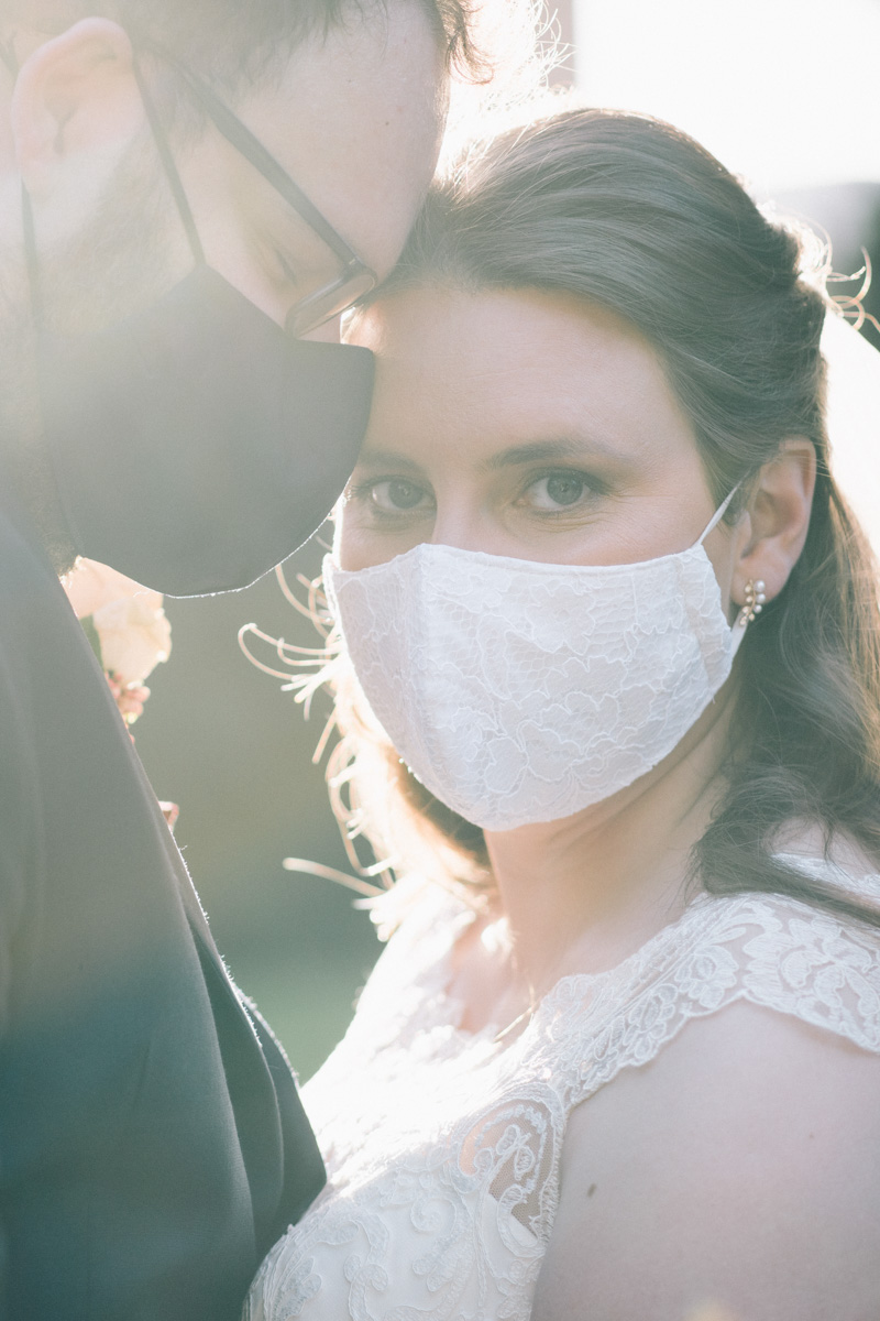 bride and groom with masks on