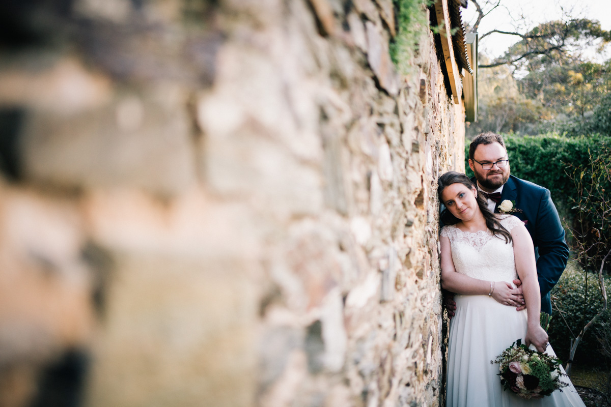 bride and groom leaning against wall in adelaide botanic gardens