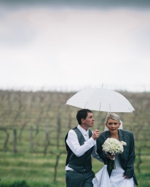Groom holding umbrella